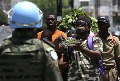 A demonstrator eats grass in front of a U.N. peacekeeping soldier during a protest against the high cost of living in Port-au-Prince